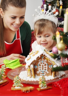 母と娘がクリスマスにジンジャーブレッドハウスを飾る