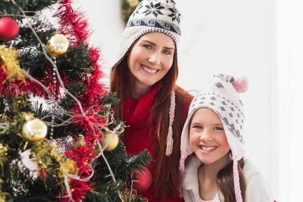 母、娘、クリスマスツリーを飾る