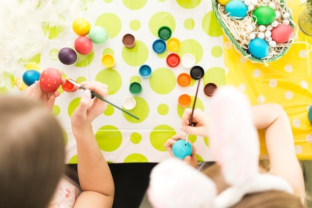 Мать и дочь украшают пасхальные яйца