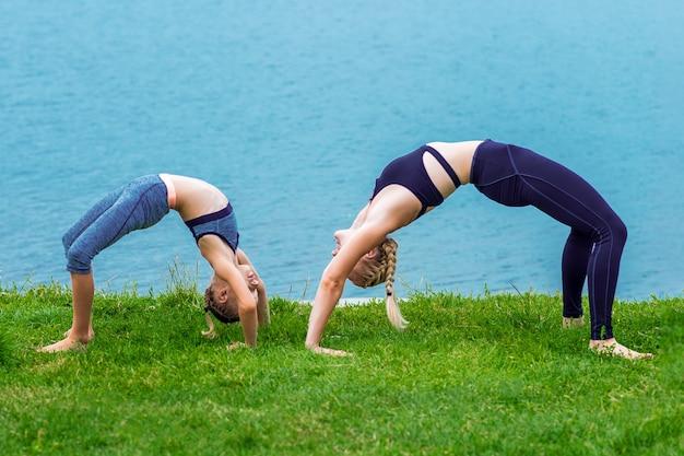 Мать и дочь делают упражнения на берегу