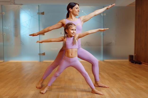 Мать и дочь делают упражнения в тренажерном зале, фитнес-тренировки. мама и маленькая девочка в спортивной одежде, совместные тренировки в спортклубе