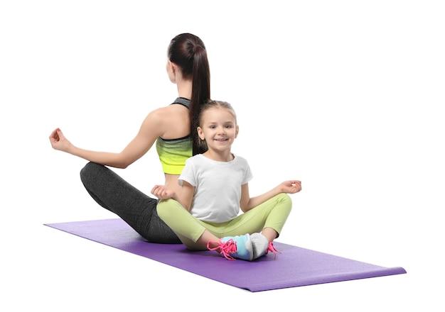 Мать и дочь делают упражнения на белом фоне