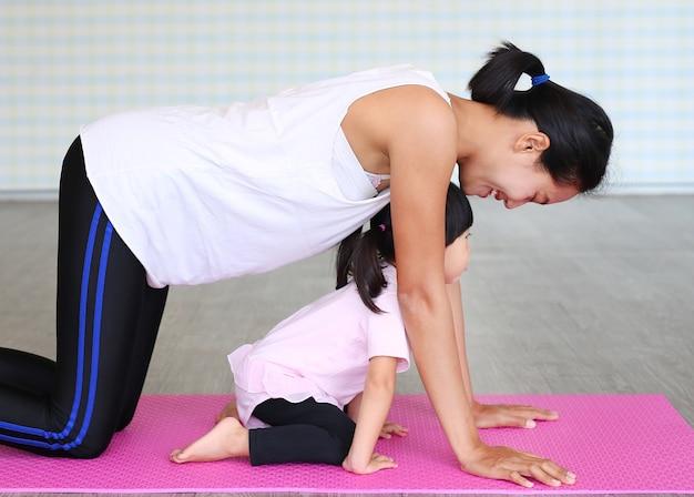 Мать и дочь делают упражнения или йога