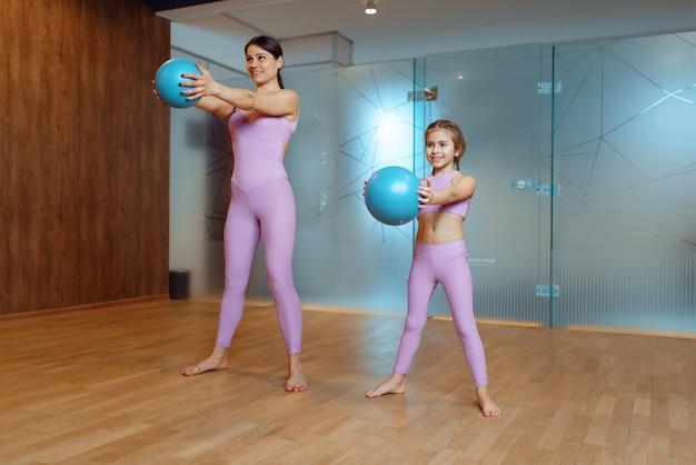 Мать и дочь делают упражнения с мячами в тренажерном зале, фитнес-тренировки. мама и маленькая девочка в спортивной одежде, совместные тренировки в спортивном клубе