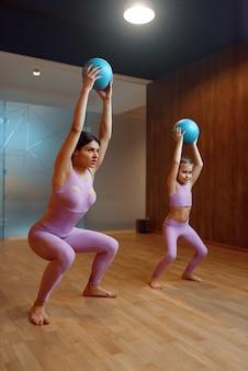Мать и дочь делают упражнения с мячами в тренажерном зале, фитнес-тренировки. мама и маленькая девочка в спортивной одежде, совместные тренировки в спортклубе