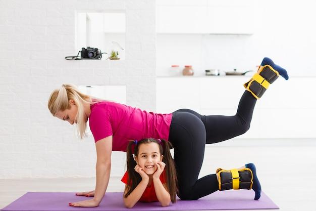 Мать и дочь делают упражнения на коврике дома.