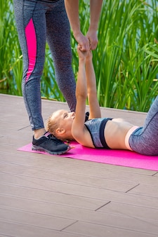Мать и дочь делают упражнения в спортзале
