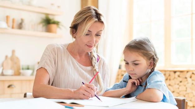 Мать и дочь делают домашнее задание дома