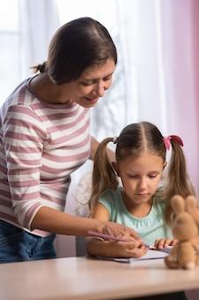 Мать и дочь вместе дома делают домашнее задание из школы. мама помогает дочери делать домашнее задание