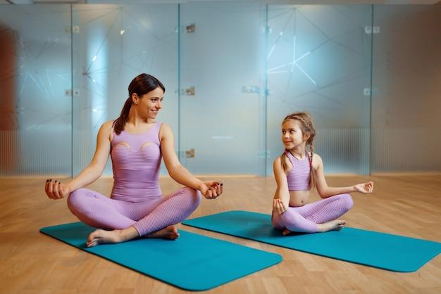 Мать и дочь делают упражнения на расслабление на циновках в тренажерном зале, тренировки йоги. мама и маленькая девочка в спортивной одежде, совместные тренировки в спортивном клубе