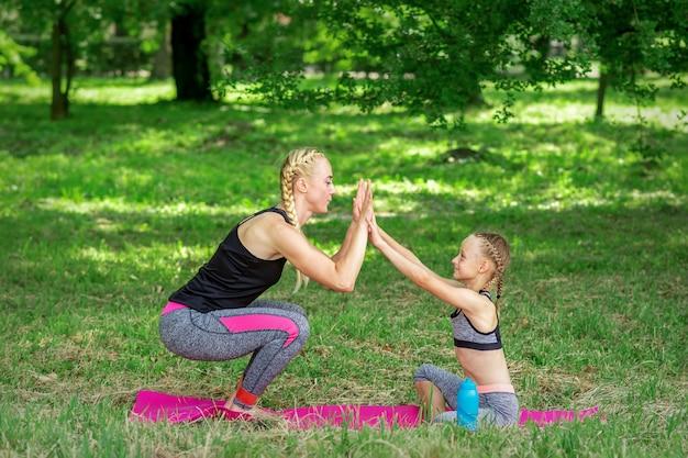 Мать и дочь делают спортивные упражнения на коврике в парке на открытом воздухе