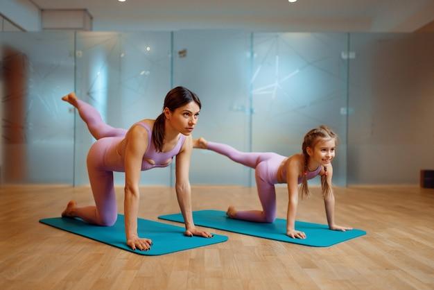 Мать и дочь делают упражнения на растяжку на циновках в тренажерном зале, тренировки пилатеса. мама и маленькая девочка в спортивной одежде, совместные тренировки в спортивном клубе