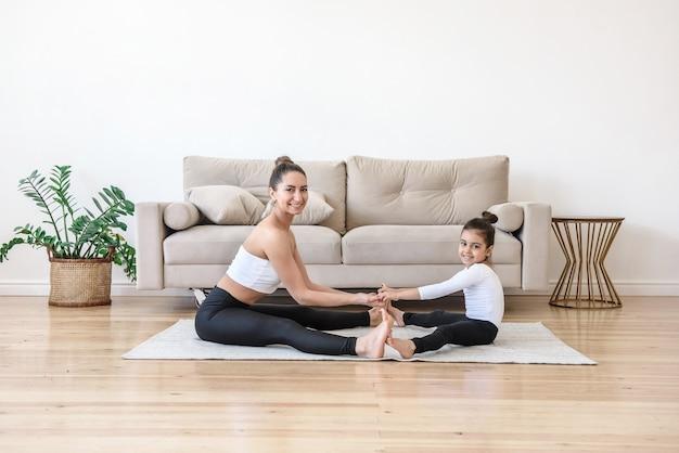 Мать и дочь вместе занимаются йогой дома