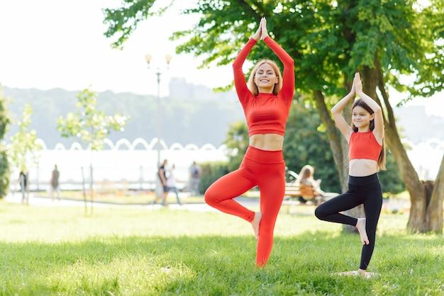Мать и дочь делают упражнения йоги на траве в парке в дневное время