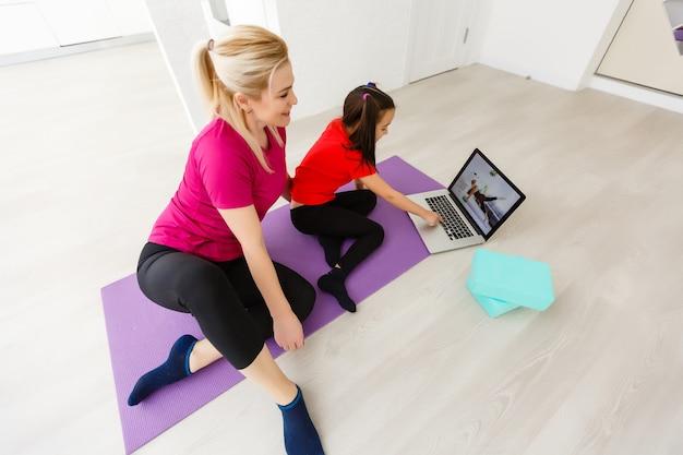 Мать и дочь делают упражнения йоги на коврике дома.