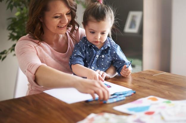 Мать и дочь, опираясь на белой бумаге