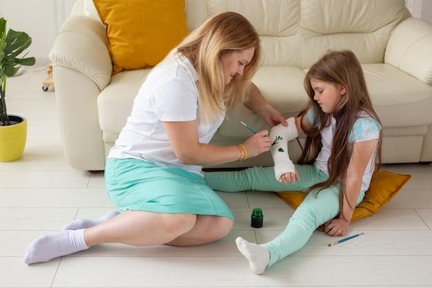페인트 놀이 치료 개념을 사용하여 붕대에 엄마와 딸 그림 그리기