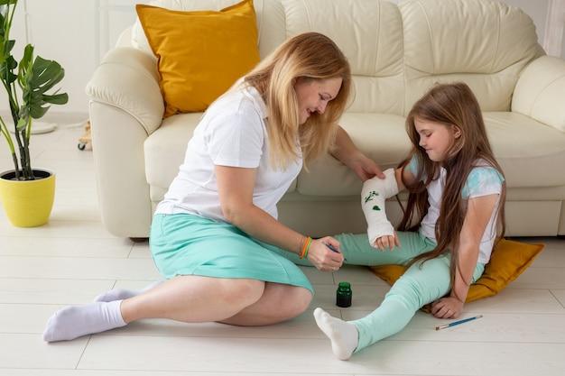 母と娘が絵の具を使って包帯に絵を描く遊戯療法の概念
