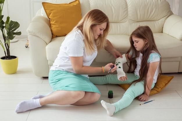 페인트 놀이 치료 개념을 사용하여 붕대에 그림을 그리는 엄마와 딸
