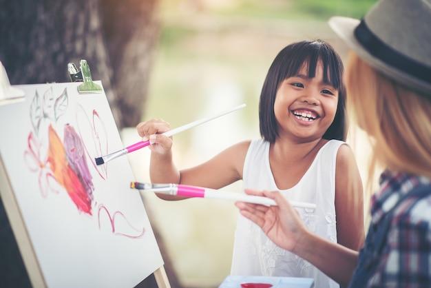 母と娘が一緒に公園に絵を描く