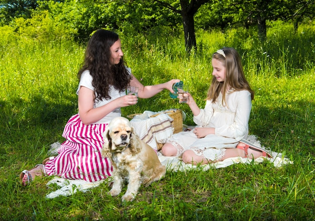 Мать и дочь пьют воду в парке