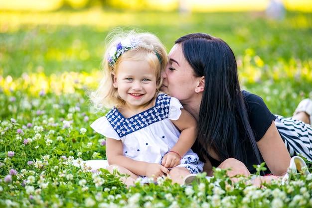 엄마와 딸 자연에서 사과 먹고. 어머니와 그녀의 아이는 이른 봄을 즐기고, 사과를 먹고, 행복합니다.