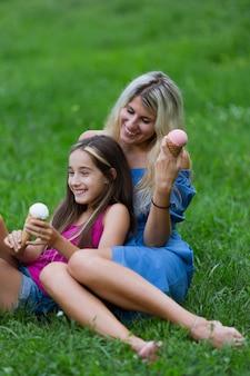 Мать и дочь едят мороженое в парке