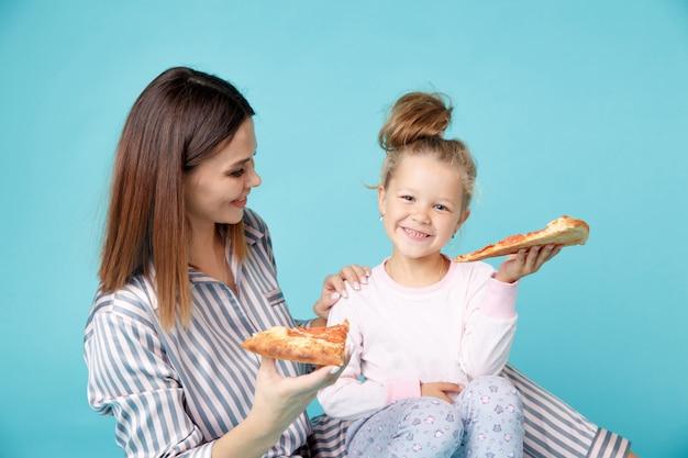 Мать и дочь едят пиццу, сидя на полу в пижаме, изолированной на синем фоне