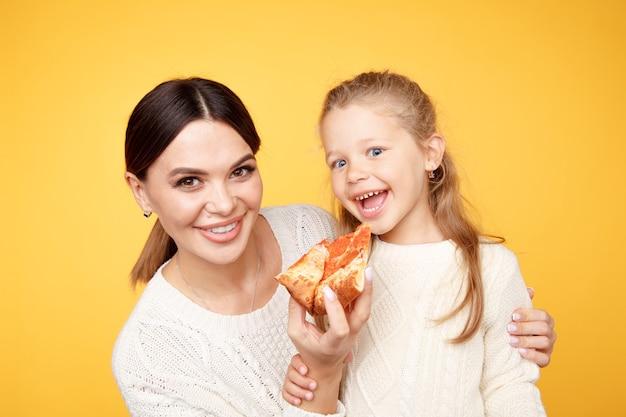 Мать и дочь вместе едят пиццу и веселятся, изолированные на желтой комнате.