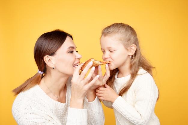 Мать и дочь вместе едят пиццу и весело изолированы над желтой студией.