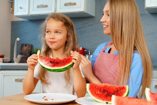 Мать и дочь едят арбуз дома на кухне
