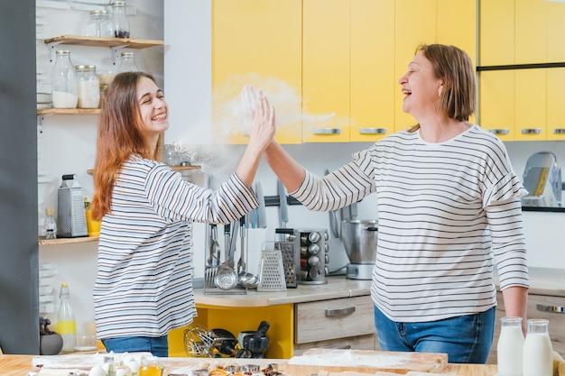 母と娘は一緒に料理を楽しんだり、ハイタッチをしたり、小麦粉を振り落としたり、笑ったりします。