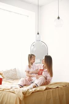 ベッドで楽しんでいる母と娘。赤いギフトボックスを持っています。母の日。