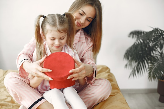 Мать и дочь наслаждаются на кровати. держа красную подарочную коробку. день матери.