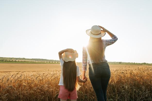 Семья матери и дочери фермеров в желтом пшеничном поле на закате ребенка женщина в шляпе на голове е ...