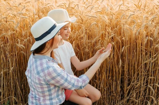 Семья матери и дочери фермеров трогает уши руками, контролирует качество уха ...