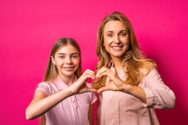 ピンクの壁に両手でハートを形成する母と娘