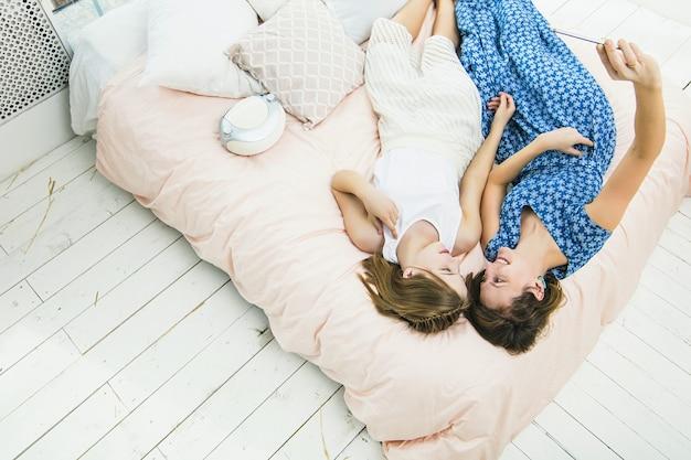 ベッドの寝室で携帯電話で幸せで美しい家を自分撮りする母と娘の女の子