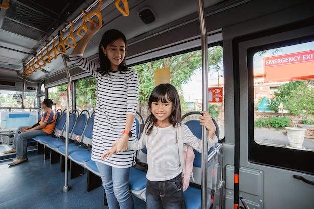 朝、公共バスで通学する母と娘