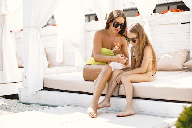 엄마와 딸이 일광욕을 하려고 합니다. 수영장 옆에 앉아 있는 어린이들에게 자외선 차단제를 바르는 부모.