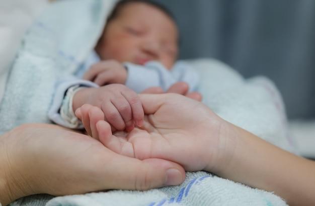 生まれたばかりの赤ちゃんの妹の指を持っている母と娘の手、家族の概念の新しい生活