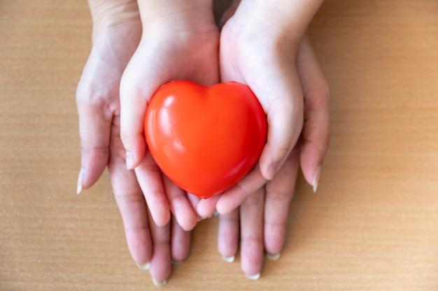 赤いハート、医療、寄付、家族保険の概念を保持している母と娘の手
