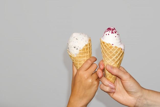 母と娘の手は、ミルクアイスクリームとアイスクリームコーンを保持しています。灰色の壁に分離