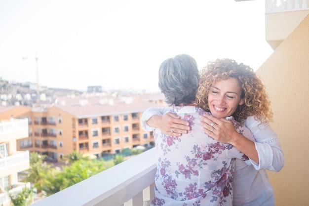도시와 건물을 볼 수있는 테라스에서 집에서 사랑과 행복 야외와 함께 포옹 어머니와 딸 행복 백인 사람들