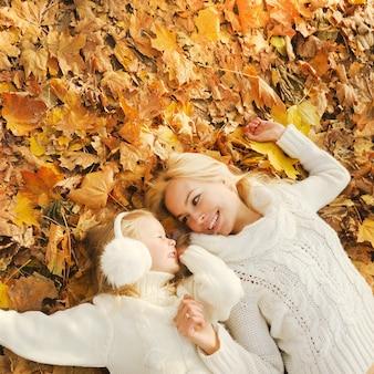 Мать и дочь веселятся в осеннем парке, лежа в желтой осенней листве и глядя друг на друга