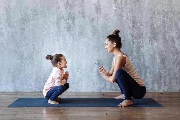 Мать и дочь весело проводят время, занимаясь спортом, занимаясь йогой и растяжкой