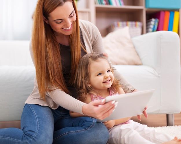 母と娘はデジタルタブレットを使用しながら楽しんでいます