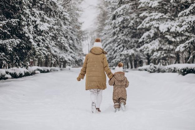 Мать и дочь веселятся в парке, полном снега