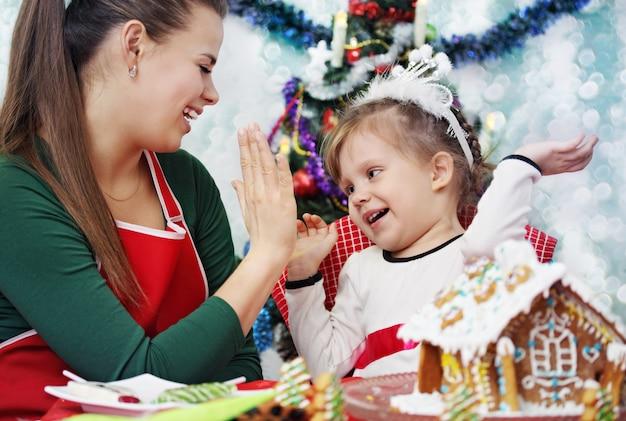 Мать и дочь весело украшают пряничный домик