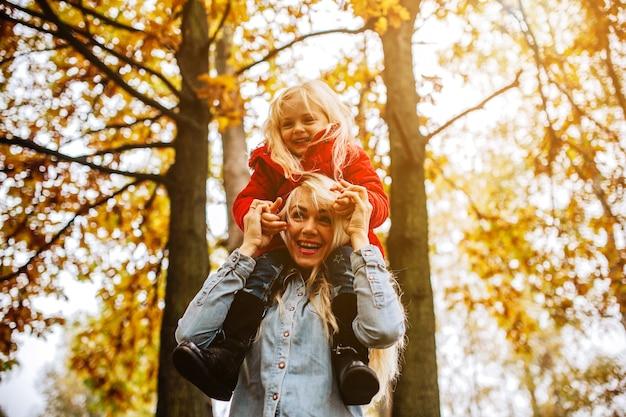 秋の公園で楽しんでいる母と娘